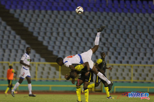 Photo: St Ann's Rangers left back Jelani Peters (top) climbs over the top of Defence Force midfielder Kerry Joseph during yesterday's Pro League action. (Courtesy Chevaughn Christopher/Wired868)