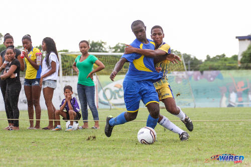 Photo: Shiva Boys HC defender Ryan Davis (left) holds off Fatima College midfielder Joshua Araujo-Wilson during SSFL action yesterday at Mucurapo Road. (Courtesy Sinead Peters/Wired868)