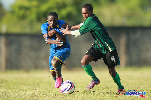 Photo: Shiva Boys Hindu College winger Quinn Rodney (left) tries to escape from a Carapichaima East Secondary defender during a 2015 SSFL contest. (Courtesy Allan V Crane/Wired868)