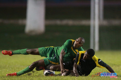 Photo: A WASA FC player) (right) makes a crunching tackle on a Stokely Vale opponent during CNG National Super League action. (Courtesy Allan V Crane/Wired868)