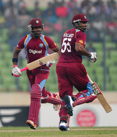 Photo: Dwayne Bravo (right) and Kieron Pollard cross for a run during active duty for the West Indies Cricket Tea,. (Copyright AFP 2015)