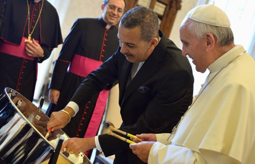 Photo: Trinidad and Tobago President Anthony Carmona (second from right) shows Pope Francis how to beat iron. (Courtesy whensteeltalks.com)