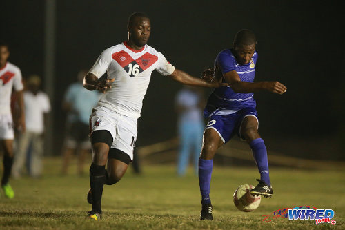 Photo: Defence Force midfielder Josimar Belgrave (right) tries to elude a Tobago FC Phoenix 1976 player during CNG National Super League action last week at the Canaan Recreational Grounds, Tobago. (Courtesy Allan V. Crane/Wired868)