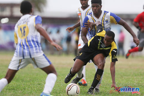 Photo: St Benedict's College attacker Marlon Phillip (right) tries to find a way through the Fatima College defence during SSFL action. (Courtesy Chevaughn Christopher/Wired868)