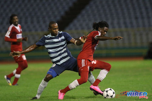 Photo: Central FC winger Jason Marcano (right) tries to elude Police FC forward Makesi Lewis during 2015 First Citizens Cup quarterfinal action at the Hasely Crawford Stadium. (Courtesy Chevaughn Christopher/Wired868)