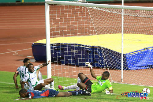 Photo: W Connection attacker Jomal Williams (second from left) diverts a low cross past Morvant Caledonia United goalkeeper Marvin Phillip (right) during Pro League action last night. (Courtesy Kerlon Orr/Wired868)