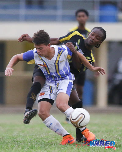 Photo: Fatima College midfielder John Michael Herrera (foreground) tries to hold off St Benedict's College midfielder Shakille Williams in SSFL action yesterday. (Courtesy Chevaughn Christopher/Wired868)