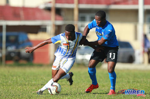 Photo: Fatima College attacker Krishorn Alexander (left) troubles Naparima College midfielder Shane Sandy during SSFL action on Mucurapo Road. (Courtesy Allan V Crane/Wired868)