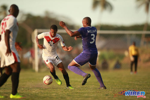Photo: Tobago FC Phoenix 1976 midfielder Aqui Raymond (centre) takes on Defence Force player Keston Williams during 2015 CNG NSL Premiership Division action. (Courtesy Allan V Crane)
