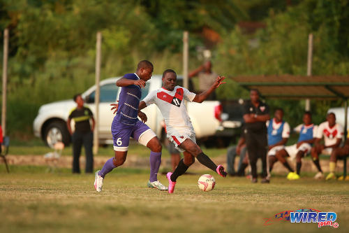 Photo: Tobago FC Phoenix 1976 attacker Le'jandro Williams (right) tries to elude a Defence Force player during CNG National Super League action in Canaan, Tobago. (Courtesy Allan V Crane/Wired868)