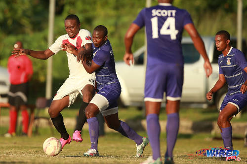 Photo: Tobago FC Phoenix 1976 attacker Lejandro Williams (left) tries to hold off a Defence Force player during CNG National Super League action last week at the Canaan Recreational Grounds, Tobago. (Courtesy Allan V. Crane/Wired868)