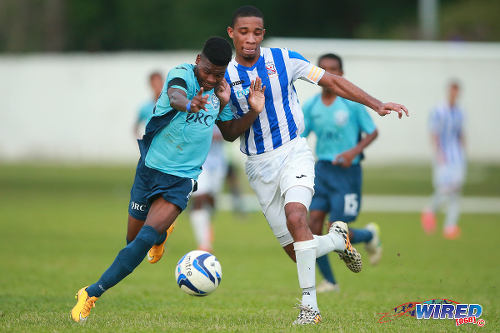 Photo: Queen's Royal College (QR) attacker Demetri Dunkley (left( bustles past St Mary's College and defender Jerome Dempster-Babb during SSFL action yesterday at St Mary's College grounds in St Clair.  QRC won 0-3  (Courtesy Allan V Crane/Wired868)