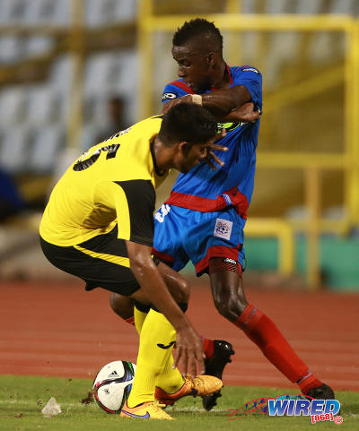 Photo: St Ann's Rangers attacker Kadeem Corbin (right) wriggles past Club Sando defender Amritt Gildharry during Pro League action yesterday. (Courtesy Kerlon Orr/Wired868)