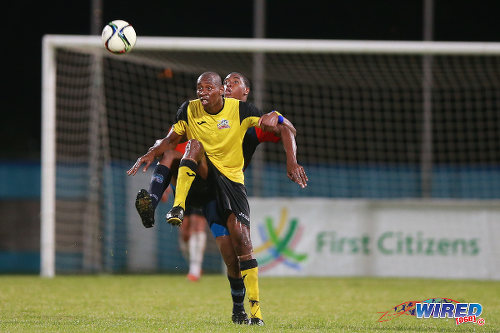 "Photo: Club Sando striker Kevon ""Showtime"" Woodley holds off a Morvant Caledonia United defender during the 2015 First Citizens Cup third place play off. (Courtesy Allan V Crane/Wired868)"