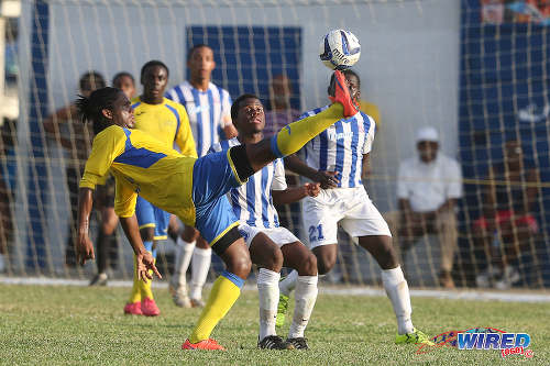 Photo: Shiva Boys HC mdifielder Yohannes Richardson (left) controls the ball while St Mary's College forward Chinua Bernard looks on during 2015 SSFL action at Serpentine Road. (Courtesy Chevaughn Christopher/Wired868)