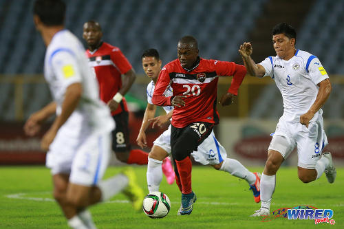 "Photo: Trinidad and Tobago playmaker Keron ""Ball Pest"" Cummings (centre) tries to find space between the lines against Nicaragua in Port of Spain on 26 October 2015. (Courtesy Allan V Crane/Wired868)"