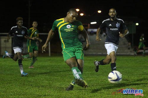 Photo: Barrackpore United right back Kevon Forrester (centre) passes the ball while Saddle Hill midfielder Sean Ramdoo (right) looks on during CNG National Super League (NSL) Championship Division action in Barrackpore. (Courtesy Chevaughn Christopher/Wired868)