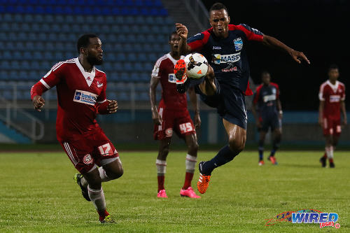Photo: Morvant Caledonia United midfielder Densill Theobald (right) controls the ball while Central FC defender Marcelle Francois looks on during 2015 Toyota Classic quarterfinal action. (Courtesy Chevaughn Christopher/Wired868)
