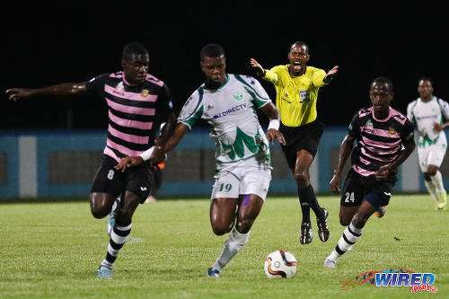 Photo: Referee Rodphin Harris (background) waves play on as W Connection striker Dwight Quintero (centre) tries to keep possession from North East Stars players Neveal Hackshaw (left) and Adrian Noel during 2015 Toyota Classic quarterfinal action. (Courtesy Chevaughn Christopher/Wired868)
