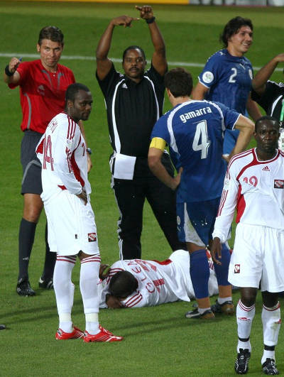 Photo: Strength and conditioning coach Zeph Nicholas (top) motions for a substitution as Trinidad and Tobago attacker Cornell Glen (bottom) lies injured on the ground during 2006 World Cup action against Paraguay. Looking on are captain Dwight Yorke (right) and Stern John. (Copyright AFP 2015)