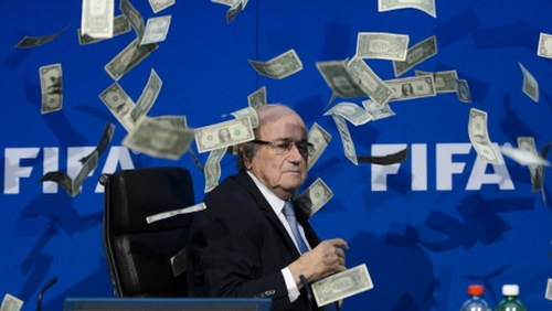 Photo: My money ha ha... FIFA president Sepp Blatter falls victim to a prank during a press conference. (Copyright CBC)