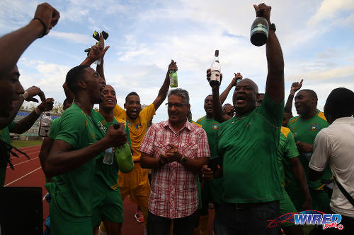 Photo: Agriculture Minister Clarence Rambharat (centre) joins the celebrations with the Guaya United football club, after their 2015 CNG NSL Knock Out triumph. (Courtesy Chevaughn Christopher/Wired868)