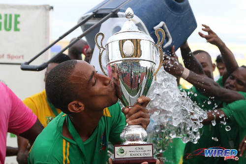 Photo: Guaya United player Kerneal Hagley enjoys a tender moment with the 2015 CNG National Super League Knock Out trophy. (Courtesy Chevaughn Christopher/Wired868)