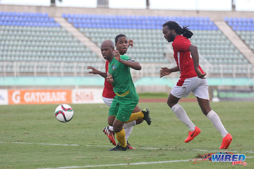 Photo: Guaya United captain, playmaker and co-coach Ryan Stewart (left) glides past Petrotrin Palo Seco defender Wayne Huyghue (right) and his teammate in the 2015 CNG National Super League KO final. (Courtesy Chevaughn Christopher/Wired868)