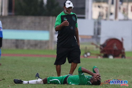 Photo: St Augustine Secondary coach Michael Grayson (standing) tries to console defensive midfielder Ainsworth Grant, after their 2-1 loss to Naparima College in the 2015 National Intercol final at the Mannie Ramjohn Stadium. (Courtesy Chevaughn Christopher/Wired868)