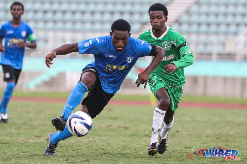 Photo: Naparima College attacker Akinola Gregory (left) motors forward under the watchful eye of St Augustine Secondary defender Kendell Boneo in the 2015 National Intercol semifinal. (Courtesy Chevaughn Christopher/Wired868)