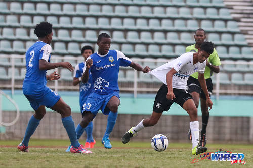 Photo: Presentation College (San Fernando) midfielder Kori Cupid (centre) tries to tug back Naparima College playmaker Justin Sadoo (right) during the South Intercol final in Marabella. (Courtesy Chevaughn Christopher/Wired868)