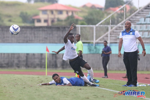 Photo: Naparima College left back Khris Stroud (centre) is taken out by a Presentation College (San Fernando) player while Pres coach Shawn Cooper (right) looks on during the South Intercol final in Marabella. (Courtesy Chevaughn Christopher/Wired868)