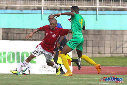 Photo: Petrotrin Palo Seco winger Lester Edwards (left) holds off Guaya United left back Kheelon Ferrier during NSL Knock Out action in 2015. (Courtesy Chevaughn Christopher/Wired868)