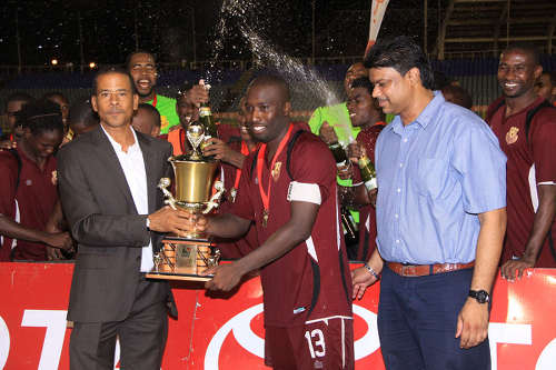 Photo: Former North East Stars striker Cornell Glen (centre) takes the 2013 Toyota Classic Cup from Pro League CEO Dexter Skeene (left) while Toyota marketing manager Sean Shaffie looks on. (Courtesy Kenroy Ambris)