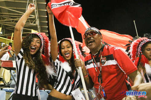 "Photo: ""Soca Warriors"" supporter Joey ""Posh"" Richardson (right) exchanges notes with some football fans during 2018 World Cup qualifying action against the United States on 17 November 2015. (Courtesy Chevaughn Christopher/Wired868)"
