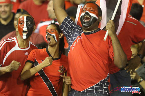 "Photo: Football fans (from left) Peter Cumberbatch, Alana Lewis and Eugene Todd answer the call to get behind the ""Soca Warriors"" against the United States. (Courtesy Chevaughn Christopher/Wired868)"