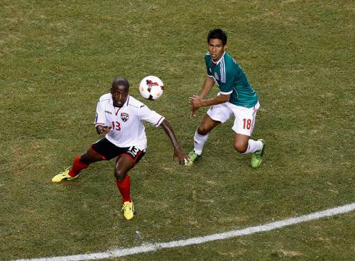Photo: Trinidad and Tobago attacker Cornell Glen (left) tries to elude a Mexico player during the 2003 CONCACAF Gold Cup. (Courtesy CONCACAF)