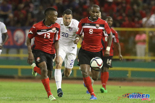 Photo: United States defender Geoff Cameron (centre) tries to keep up with Trinidad and Tobago midfielders Khaleem Hyland (right) and Cordell Cato during 2018 World Cup qualifying action at the Hasely Crawford Stadium. (Courtesy Chevaughn Christopher/Wired868)