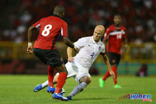 Photo: Trinidad and Tobago midfielder Khaleem Hyland (left) rolls the ball through the legs of United Staes captain Michael Bradley during 2018 World Cup qualifying action at the Hasely Crawford Stadium. (Courtesy Allan V Crane/Wired868)