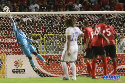 Photo: Trinidad and Tobago goalkeeper Jan-Michael Williams (left) tips a crashing drive from US midfielder Jermaine Jones (centre) on to the bar. (Courtesy Chevaughn Christopher/Wired868)
