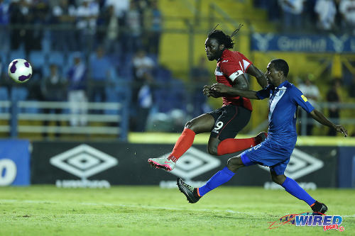 "Photo: Trinidad and Tobago captain Kenwyne Jones (left) volleys home his country's second item despite the best efforts of Guatemala defender Dennis Lopez. The ""Soca Warriors"" won their opening 2018 World Cup qualifier 2-1 in Guatemala City on 13 November 2015. (Courtesy Allan V Crane/Wired868)"