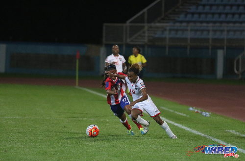 Photo: Teenaged Trinidad and Tobago flanker Chevonne John (right) takes on Puerto Rico defender Adrianna Font during 2016 Olympic qualifying action at the Ato Boldon Stadium in Couva. At present, John is with the Trinidad and Tobago National Under-20 Team in Honduras. (Courtesy Chevaughn Christopher/Wired868)