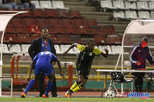 Photo: Defence Force winger Jelani Felix (right) cuts inside a Police FC opponent while his coach Marvin Gordon looks on during 2015 Pro League action last night at the Hasely Crawford Stadium. (Courtesy Allan V Crane/CA-images/Wired868)