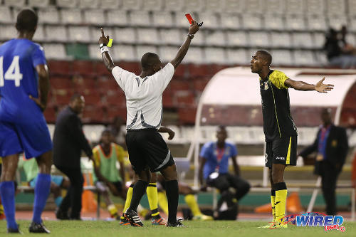 Photo: Referee Keon Yorke (centre) flashes a red card at Defence Force right back Marvin Jones (right) while his coach Marvin Gordon (second from left) looks on during 2015 Pro League action last night at the Hasely Crawford Stadium. (Courtesy Allan V Crane/CA-images/Wired868)