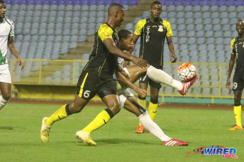 Photo: W Connection midfielder Briel Thomas (centre) controls the ball under pressure from Defence Force player Rodell Elcock in the 2015 Toyota Classic final. (Courtesy Chevaughn Christopher/Wired868)