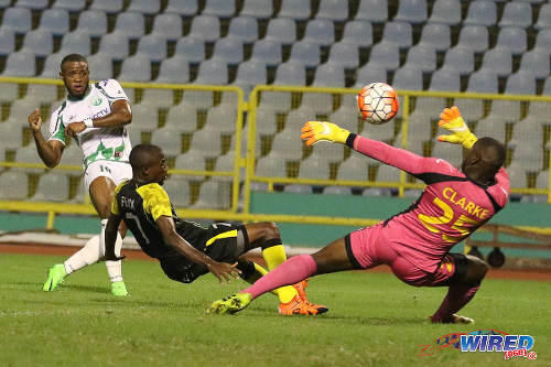 Photo: W Connection attacker Jomal Williams (left) places past Defence Force goalkeeper Sheldon Clarke and defender Jelani Felix to put his team ahead in the 2015 Toyota Classic final. (Courtesy Chevaughn Christopher/Wired868)