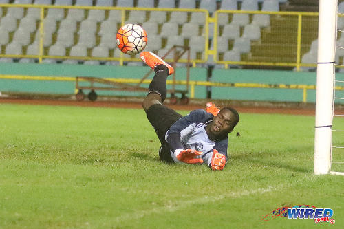 Photo: W Connection custodian Julani Archibald makes a fine low save against Defence Force in the 2015 Toyota Classic final. (Courtesy Chevaughn Christopher/Wired868)