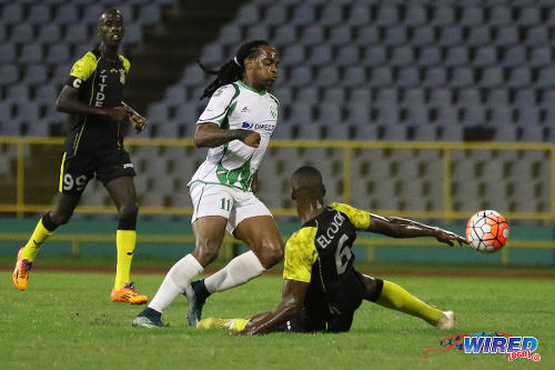 Photo: W Connection attacker Neil Benjamin Jr (centre) skips past a challenge from Defence Force stopper Rodell Elcock (right) during the 2015 Toyota Classic final. (Courtesy Chevaughn Christopher/Wired868)