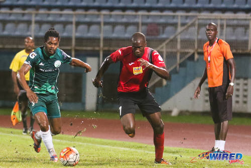 Photo: San Juan Jabloteh forward Jamal Gay (right) tries to race clear of DIRECTV W Connection defender Gerard Williams (left) during 2015/16 Pro League action in Couva. Looking on is Jabloteh assistant coach Nigel Henry. (Courtesy Chevaughn Christopher/Wired868)