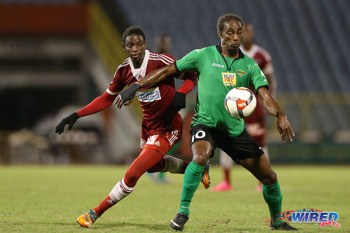 Photo: San Juan Jabloteh attacker Tyrone Charles (right) keeps the ball from Central FC right back Kaydion Gabriel during  previous 2015/6 Pro League action at the Hasely Crawford Stadium. (Courtesy Allan V Crane/CA-images/Wired868)